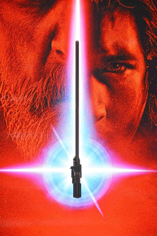 Rey handing lightsaber to Luke